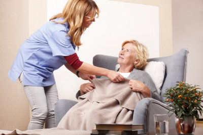 caregiver giving blanket to her patient